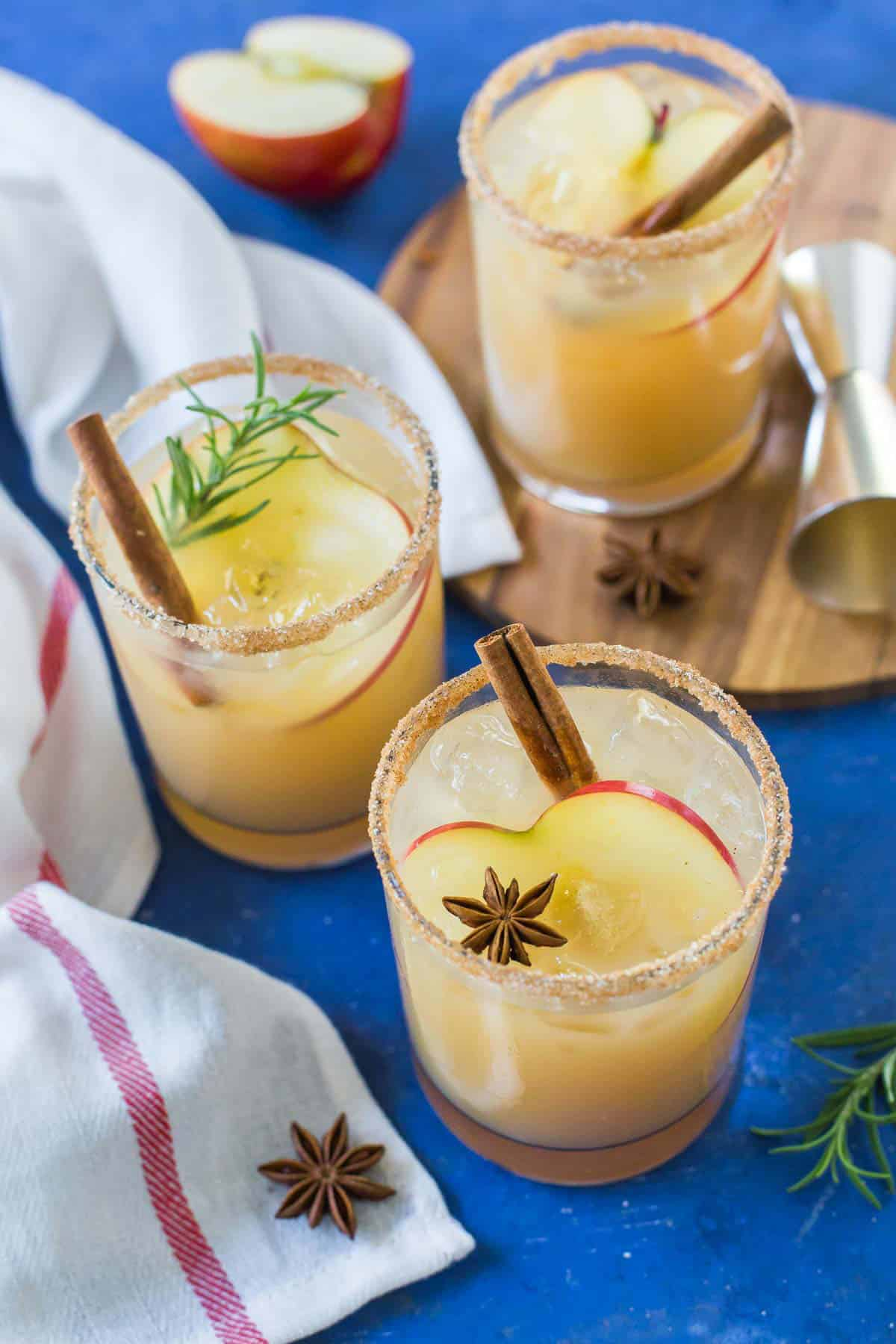 Three Apple Cider Margaritas sit on a blue background