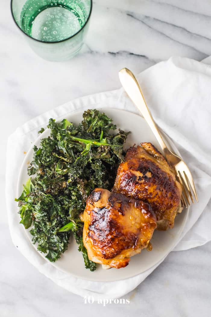 Honey Garlic Chicken Thighs served one a white plate with a side of Crispy Kale