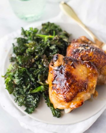 Close-up of Paleo Honey Garlic Chicken Thighs served with a side of crispy kale