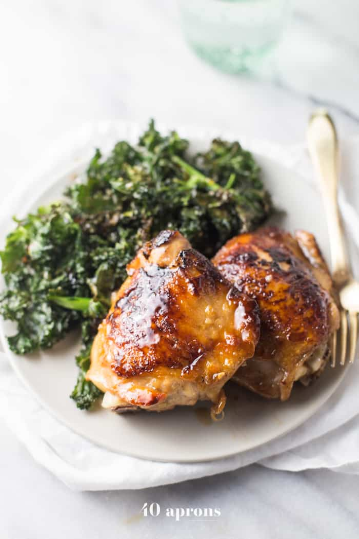 Different angle of Honey Garlic Chicken Thighs served one a white plate with a side of Crispy Kale