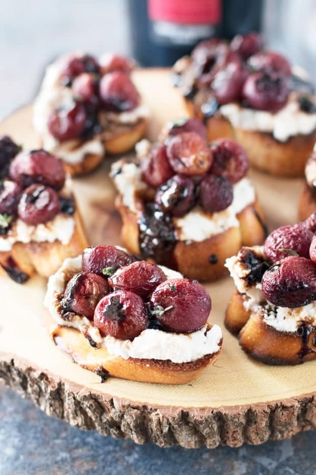 Roasted Grape Balsamic Crostini are served on a wooden board