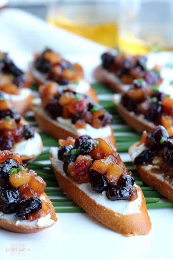A close up of several Apple Chutney Bruschetta on a white and green plate