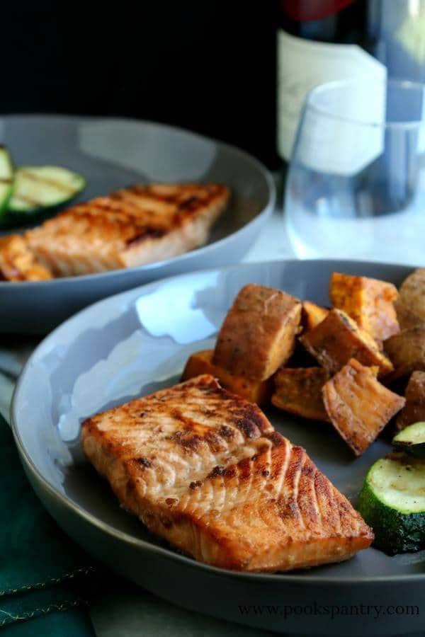 A blue plate holds a serving of Brown Sugar Bourbon Salmon with sweet potatoes and veggies