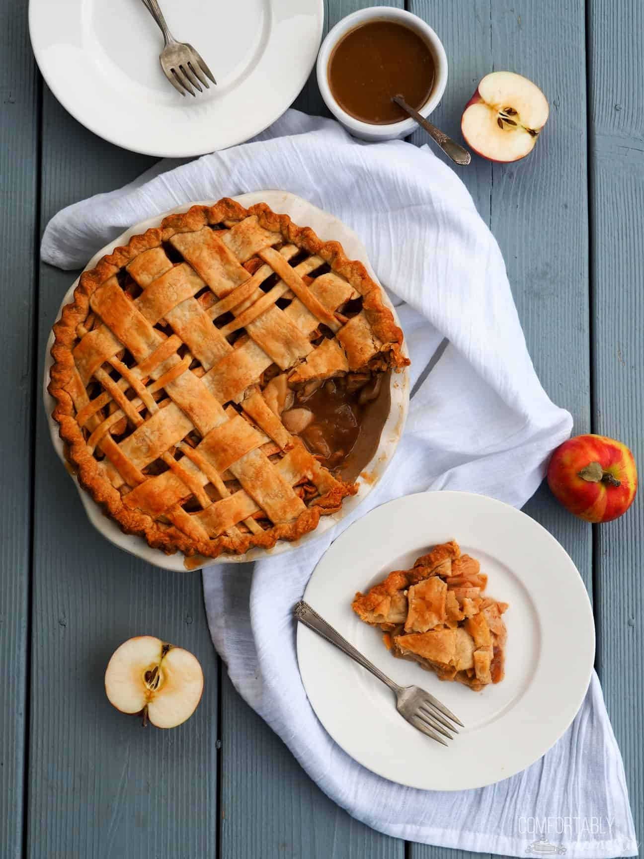 A Caramel Apple Pie with one slice cut out of it sits on a blue background on a white cloth, surrounded by apples, plates and caramel