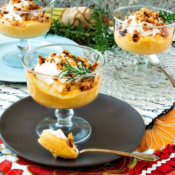 Three glass parfait cups hold orange Caramel Pumpkin Mousse, one of which has a spoonful of it scooped out