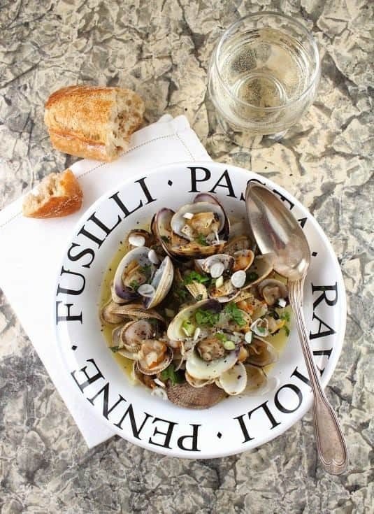A bowl of Clams in White Wine is shown with a spoon, bread and a glass of white wine