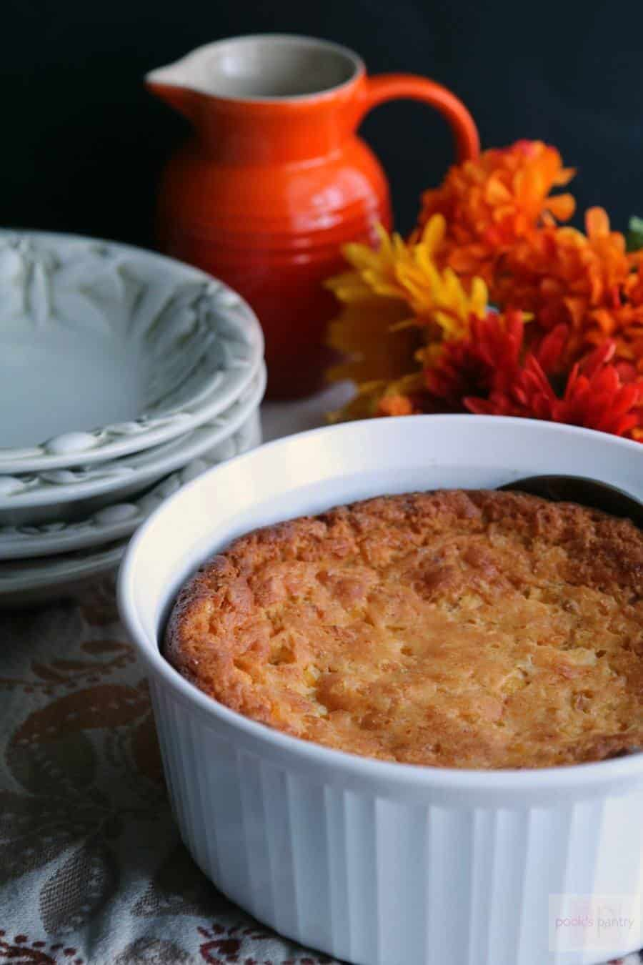 A scuffle dish holding Easiest Five Ingredient Corn Casserole is served with plates and orange flowers in the background
