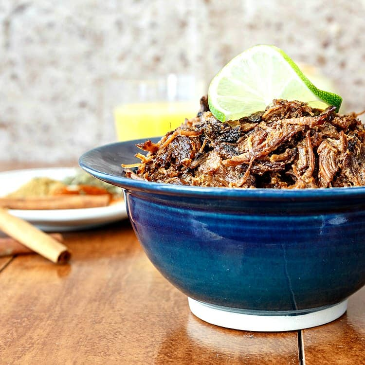 A blue bowl holds Smoky Beef Carnitas on a wooden surface