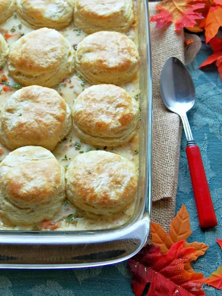 A baking dish holds Turkey Biscuit Casserole and sits on a blue background with a silver serving spoon