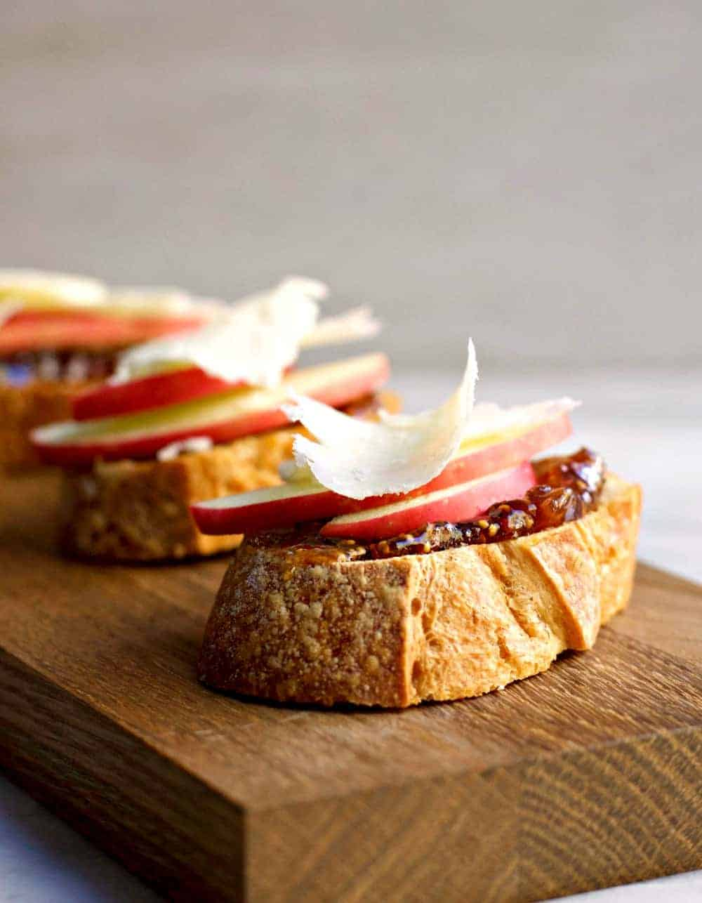 Close up of a few Apple Crostini with Fig Jam and Pecorino sitting on a wooden cutting board