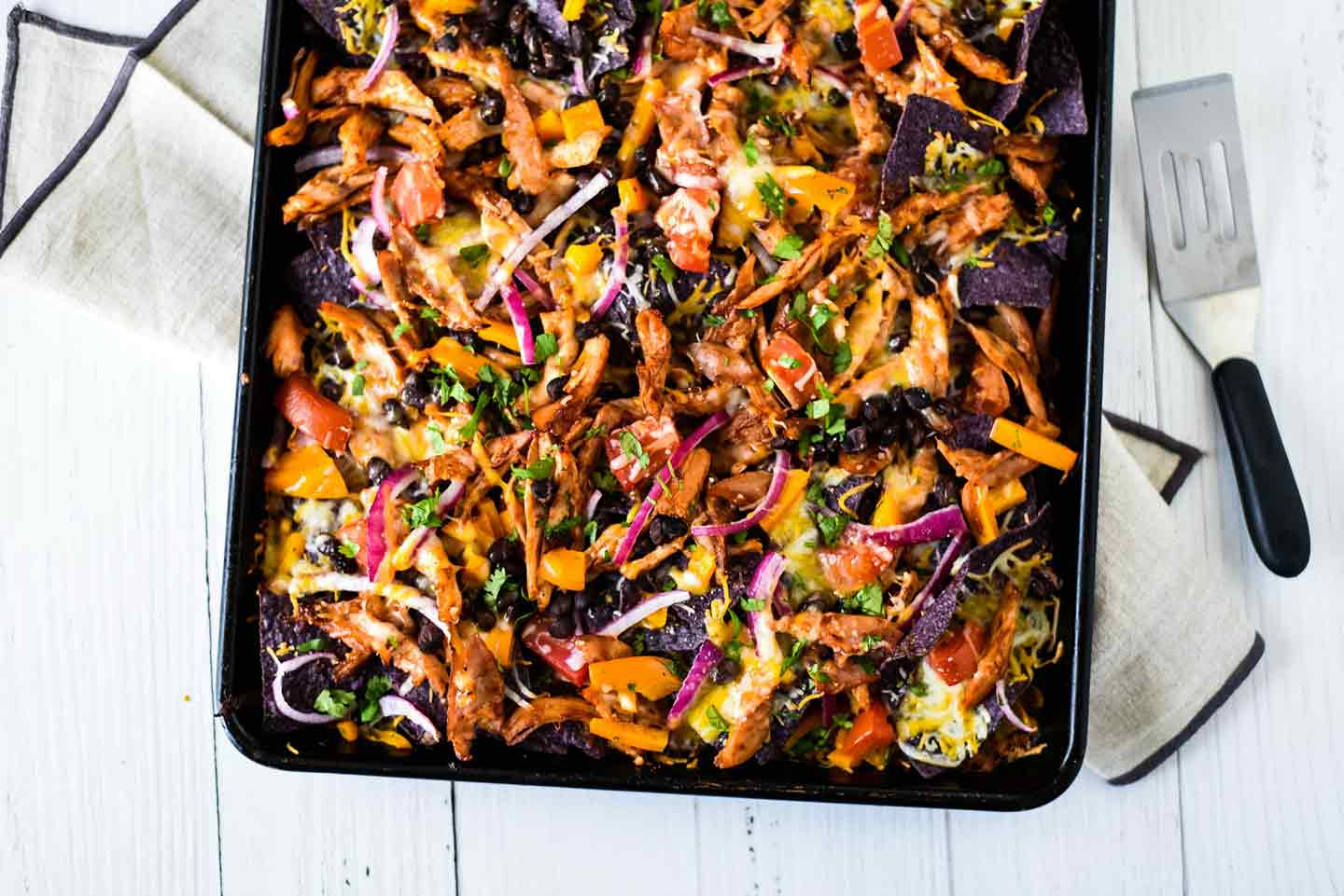 Horizontal image of Sheet Pan BBQ Chicken Nachos on a sheet pan, shown from above