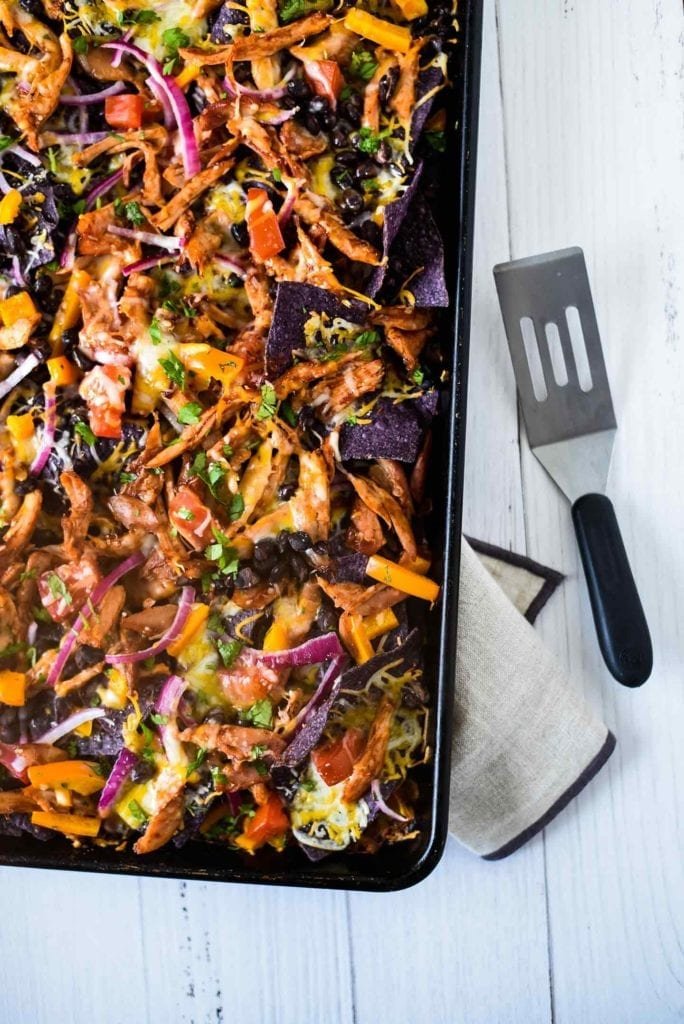 Sheet Pan BBQ Chicken Nachos shown from above on a sheet pan, ready for serving with a spatula