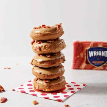 Baked Maple Bacon Donuts are stacked in front of a Wright Brand Bacon package