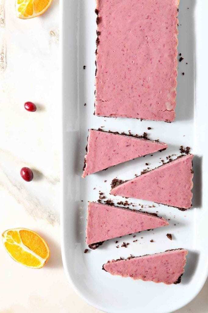 A partially sliced Creamy Cranberry Tart is served on a white platter, surrounded by orange slices and fresh cranberries