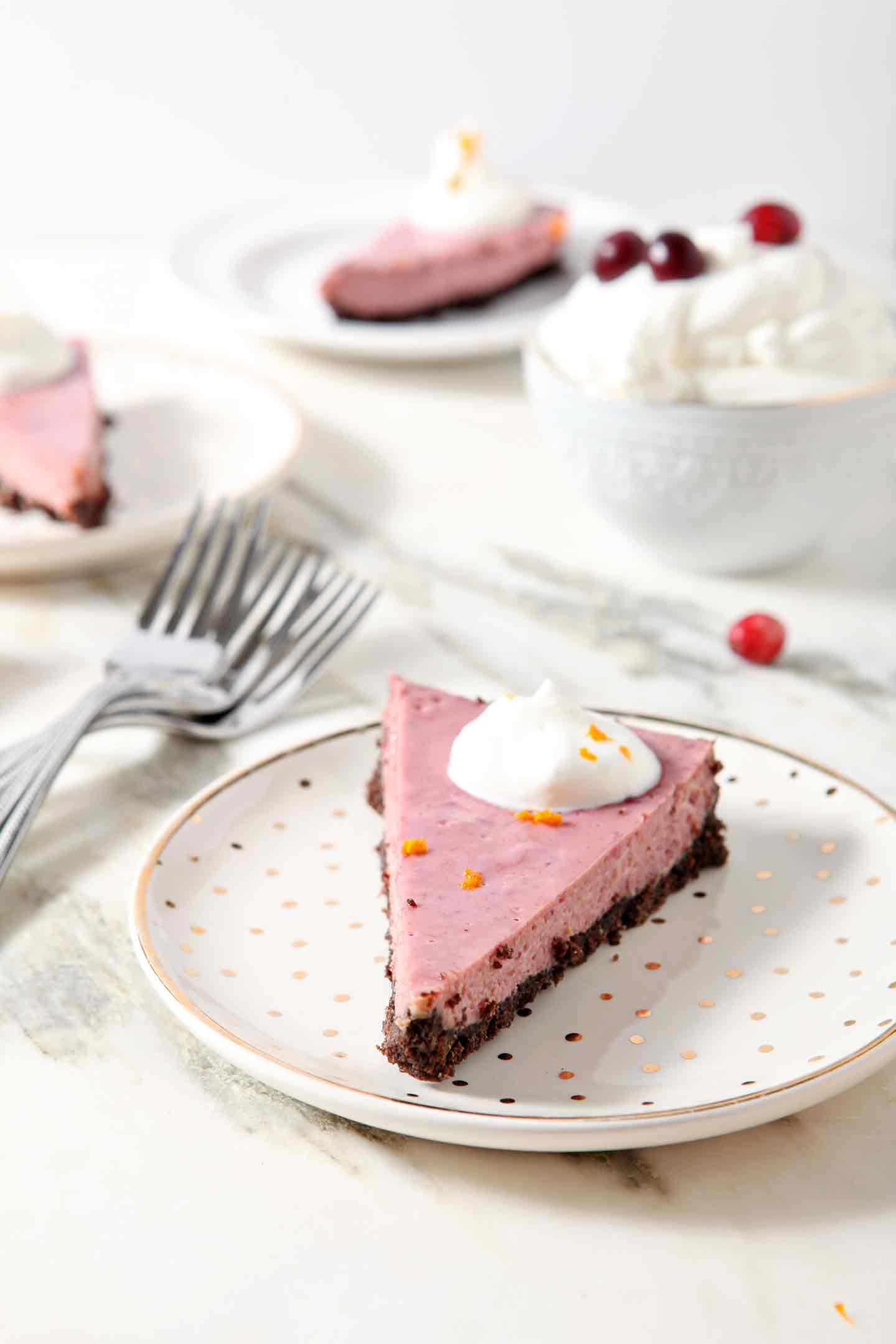 Slices of Creamy Cranberry Tart are served on gold and white plates with fresh whipped cream