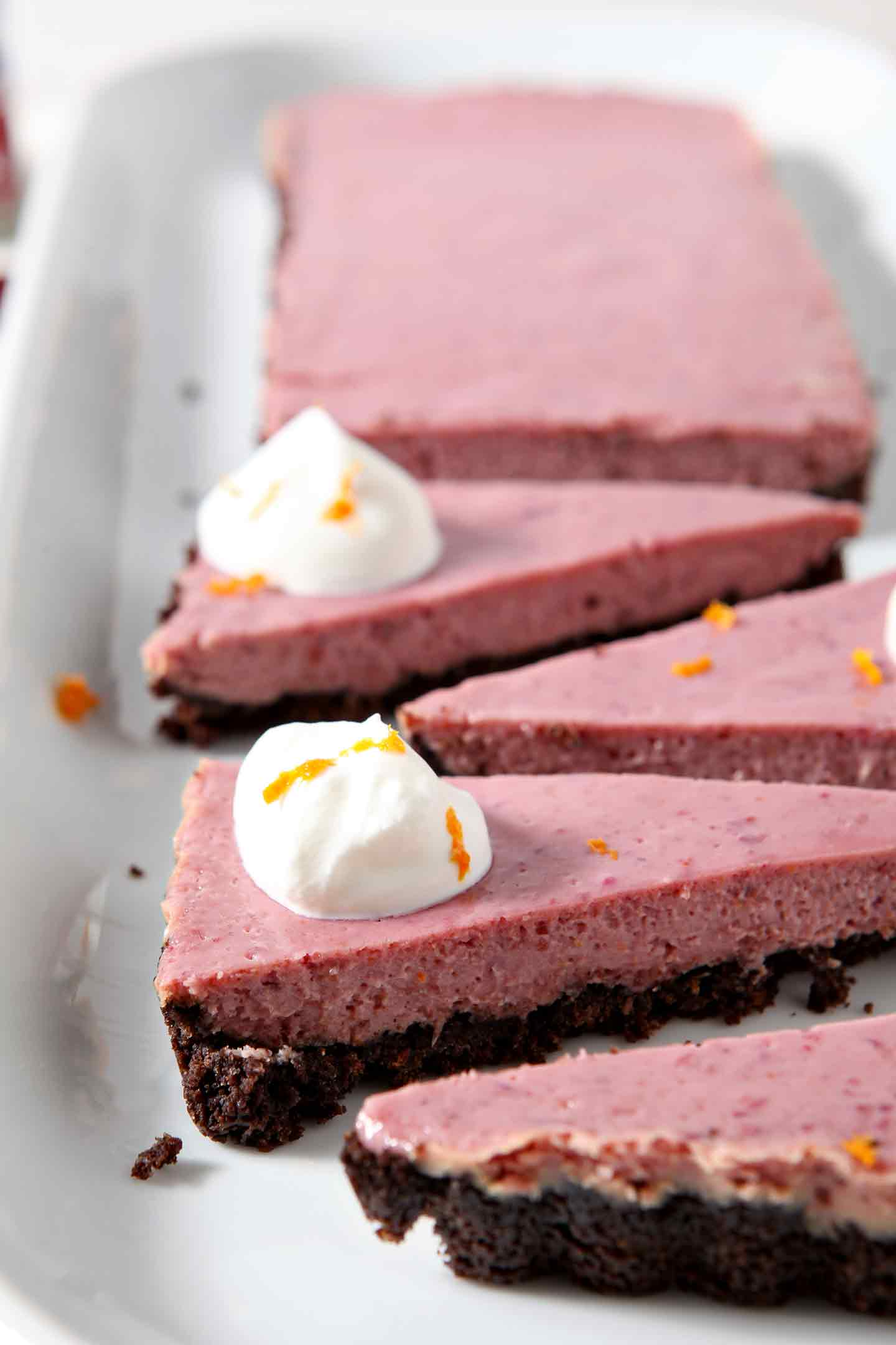 Close up of slices of Creamy Cranberry Tart, topped with fresh whipped cream