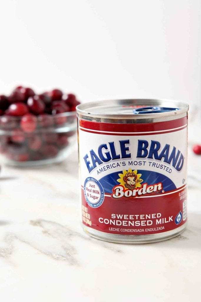 A can of Eagle Brand Sweetened Condensed Milk sits in front of a bowl of fresh cranberries