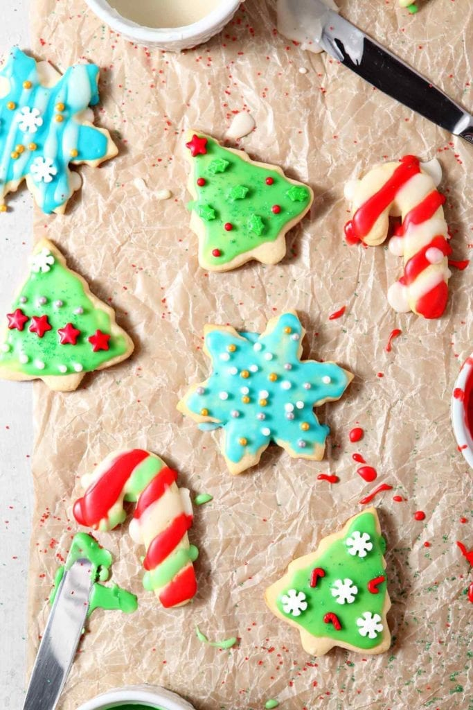 Sugar cookies, decorated and topped with Easy Sugar Cookie Icing, are set out to dry on a piece of parchment paper