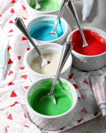Five white ramekins hold different colors of Easy Sugar Cookie Icing, ready for decorating