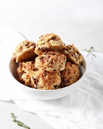 A bowl of French Onion Biscuits are shown on a white background