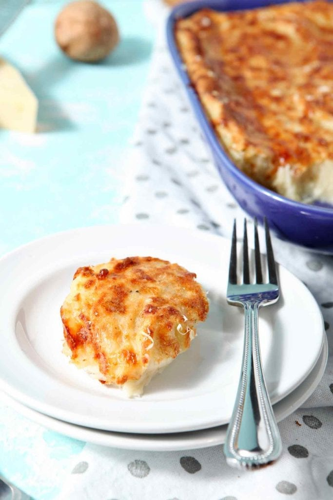 Garlic Parmesan Mashed Potato Casserole is served on a white plate with the casserole dish in the background