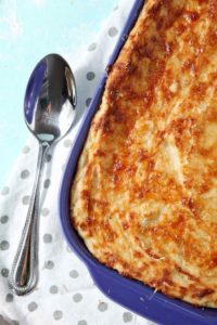 A close up of Garlic Parmesan Mashed Potato Casserole, shown in a purple baking dish with a serving spoon