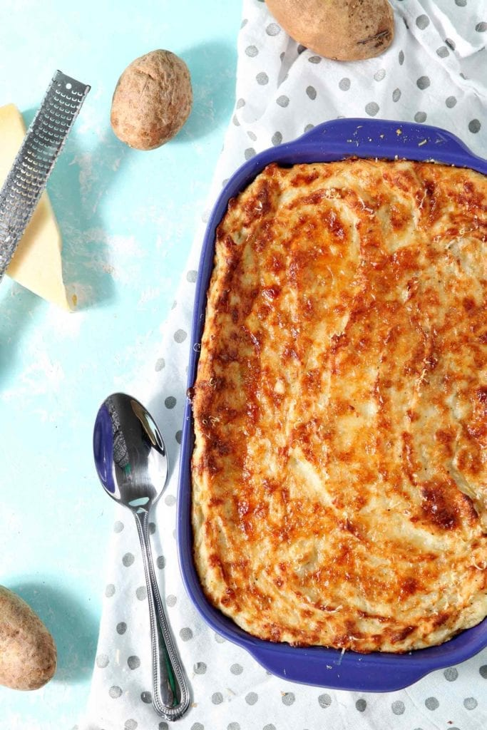 Garlic Parmesan Mashed Potato Casserole is served in its purple baking dish with a serving spoon and is surrounded by potatoes, as well as a block of parmesan cheese and a grater