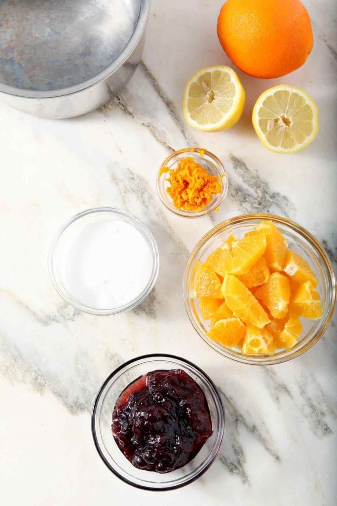 Ingredients for the Orange Cranberry Compote sit on a marble background