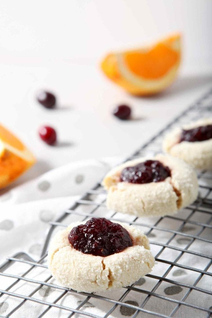 Orange Cranberry Cream Cheese Thumbprint Cookies cool on a wire cooling rack, surrounded by fresh cranberries and orange slices