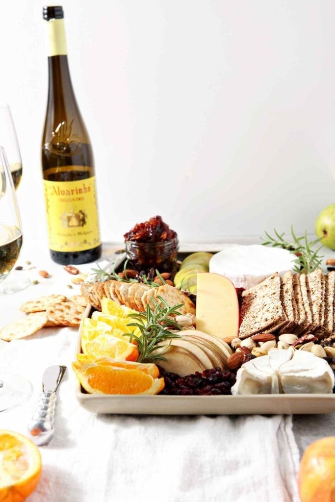 A Thanksgiving Cheese Board, served with Vinho Verde wine, sits on a grey background
