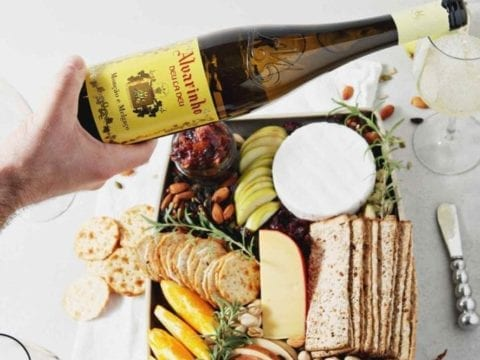 A person pours a glass of Vinho Verde wine over a Thanksgiving Cheese Board.