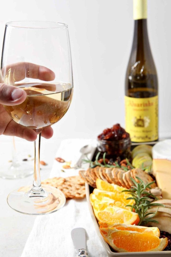 A person holds a glass of Vinho Verde wine in front of a Thanksgiving Cheese Board.