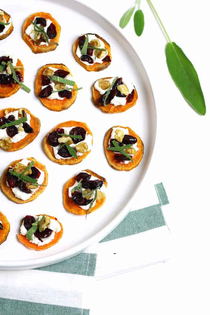 Overhead of several Holiday Sweet Potato Toast Bites sitting on a round white platter