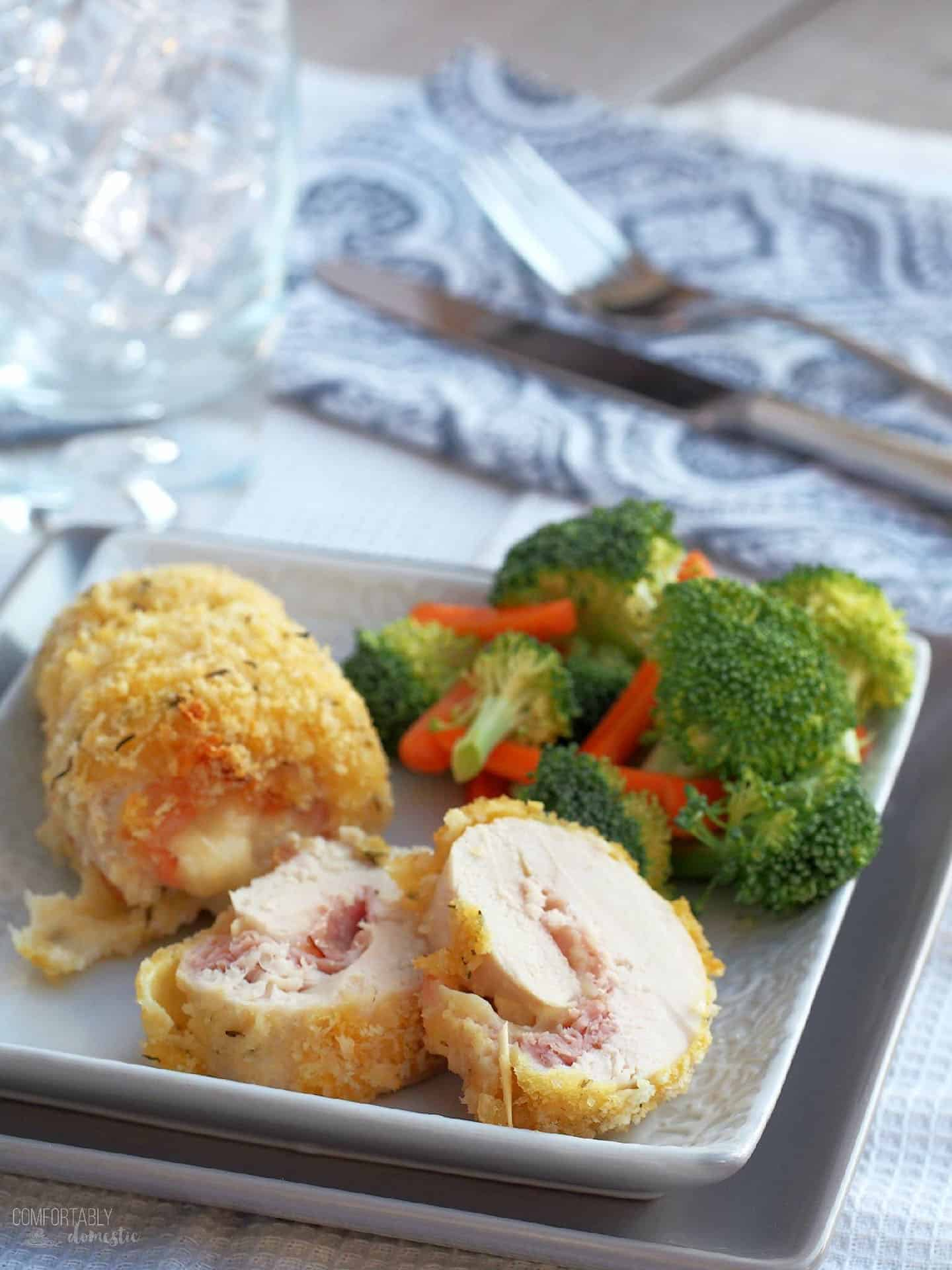 Sliced Chicken Cordon Bleu sits on a plate with steamed veggies
