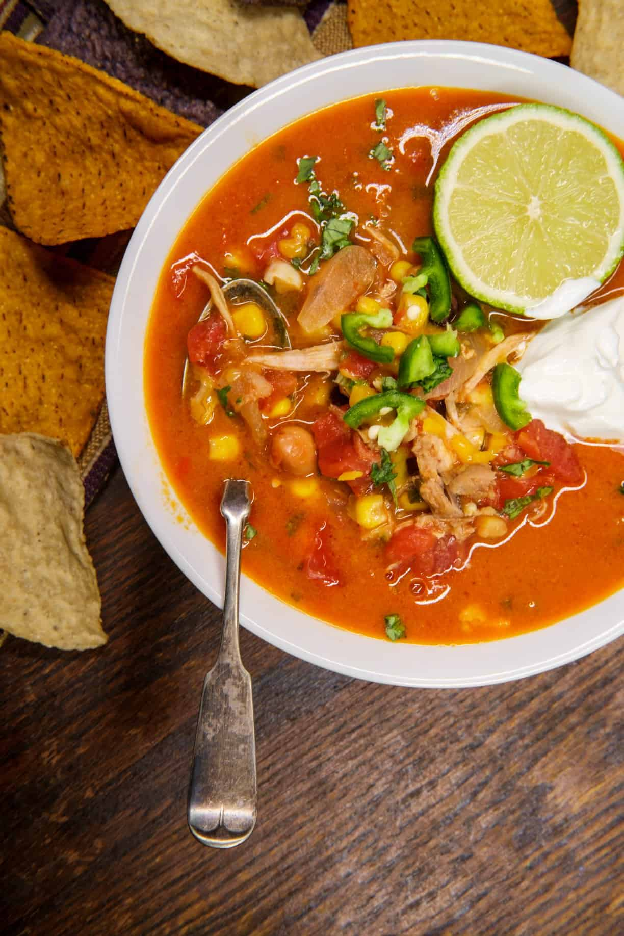 A bowl of Chicken Tortilla Soup, garnished with a lime, cilantro and sour cream, sits atop a wooden cutting board, surrounded by tortilla chips