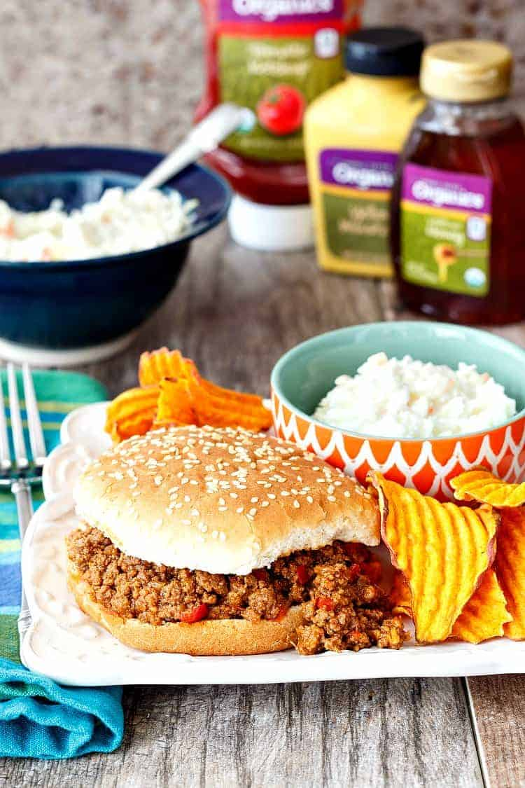 A plate holding an Easy Sloppy Joe with chips and coleslaw sits in the foreground with recipe ingredients behind it