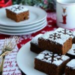A plate holding slices of Gingerbread Cake, dusted with powdered sugar to create a slowflake pattern, sits on a holiday table