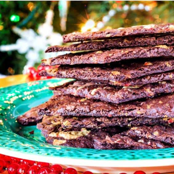 Stacked Peppermint Brownie Brittle sits on a green plate in front of a Christmas tree