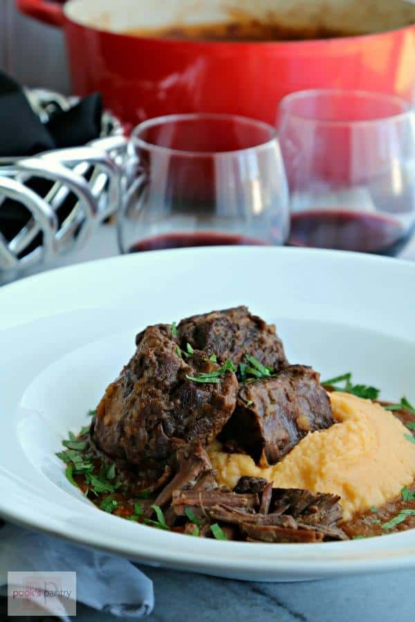 Red Wine Braised Short Ribs sit atop mashed rutabaga and are served in a white bowl