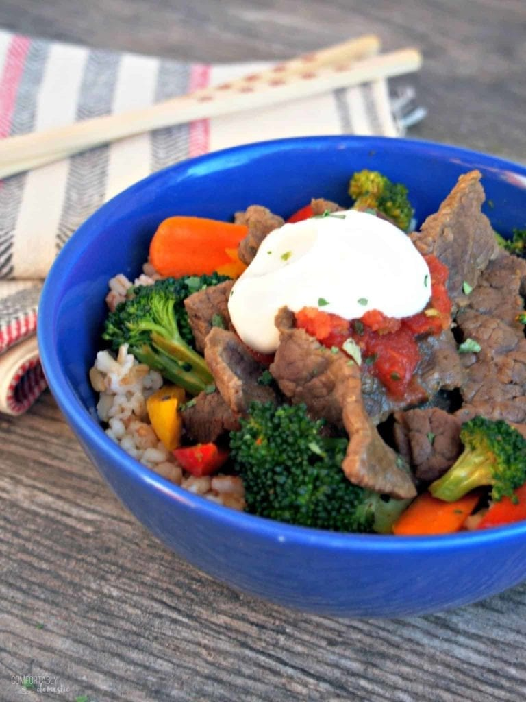 Southwest Steak Stir Fry is served in a bright blue bowl on a wooden surface