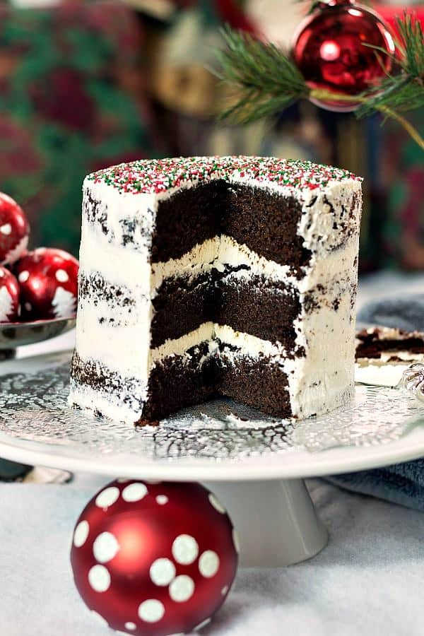 A Vegan Chocolate Christmas Cake sits on a cake stand, surrounded by Christmas decorations
