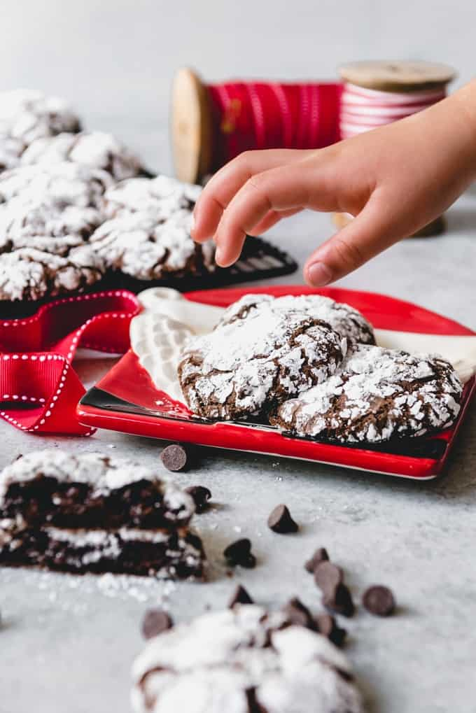 A girl grabs a cookie from a red plate holding Double Chocolate Crinkle Cookies