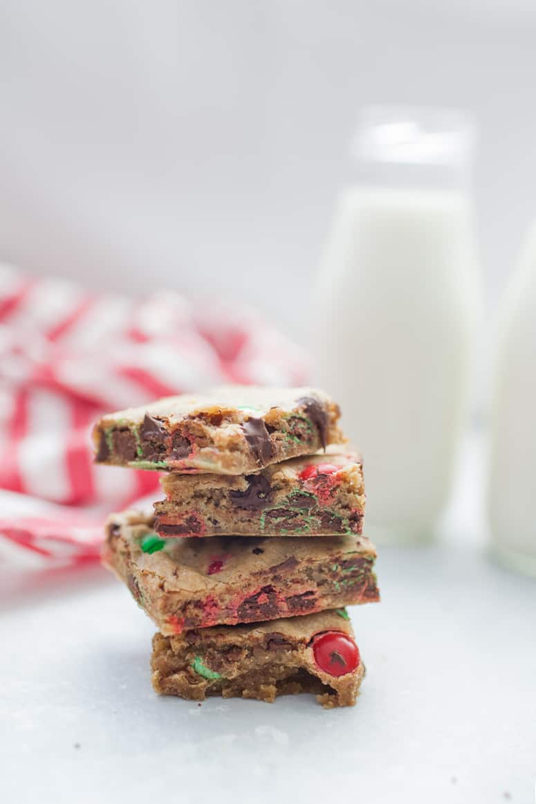 M&M Christmas Cookie Bars are stacked on top of each other and shown with a bottle of milk