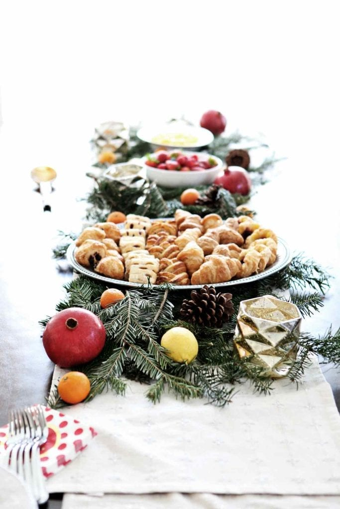 A holiday brunch table is set with pastries, fruit and scrambled eggs