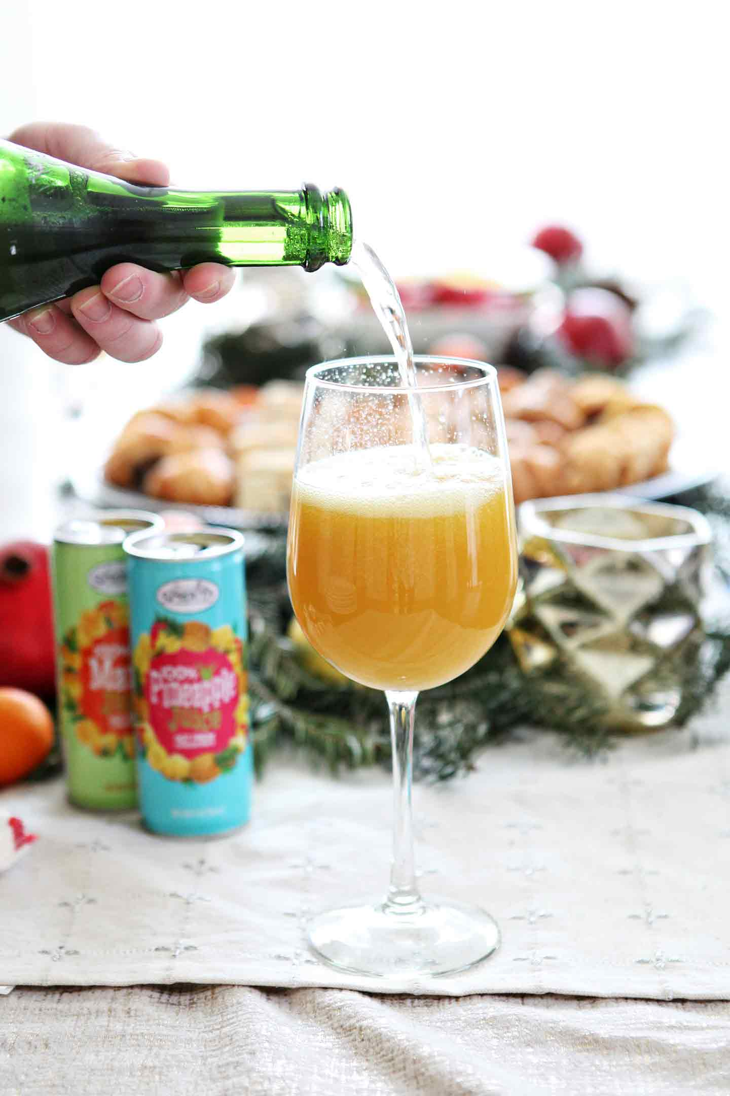 Champagne is poured into a wine glass with mango juice to make a tropical mimosa