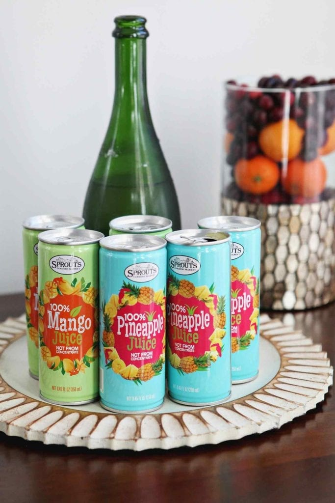 Sprouts Canned Mango and Pineapple Juices are displayed with champagne and a small fruit display on a table at an at-home holiday brunch