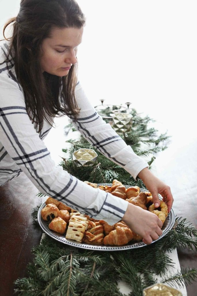 A woman arranges pastries on a silver platter before serving at a home holiday brunch