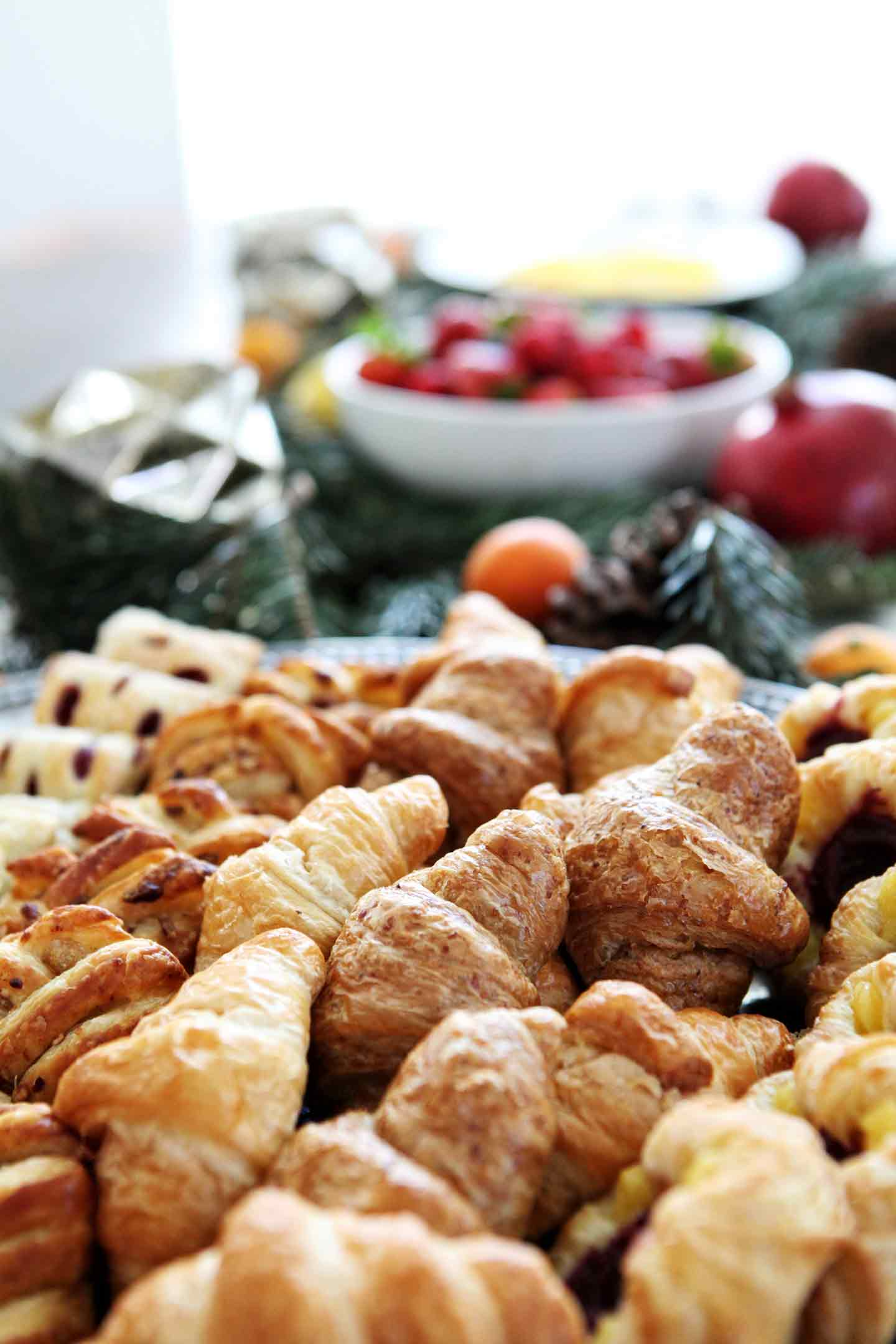Pastries are shown on a silver platter with other holiday brunch dishes shown behind them