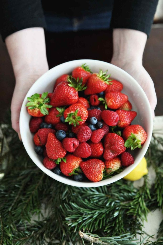 A woman holds a bowl of fresh berries over a holiday brunch tablescape