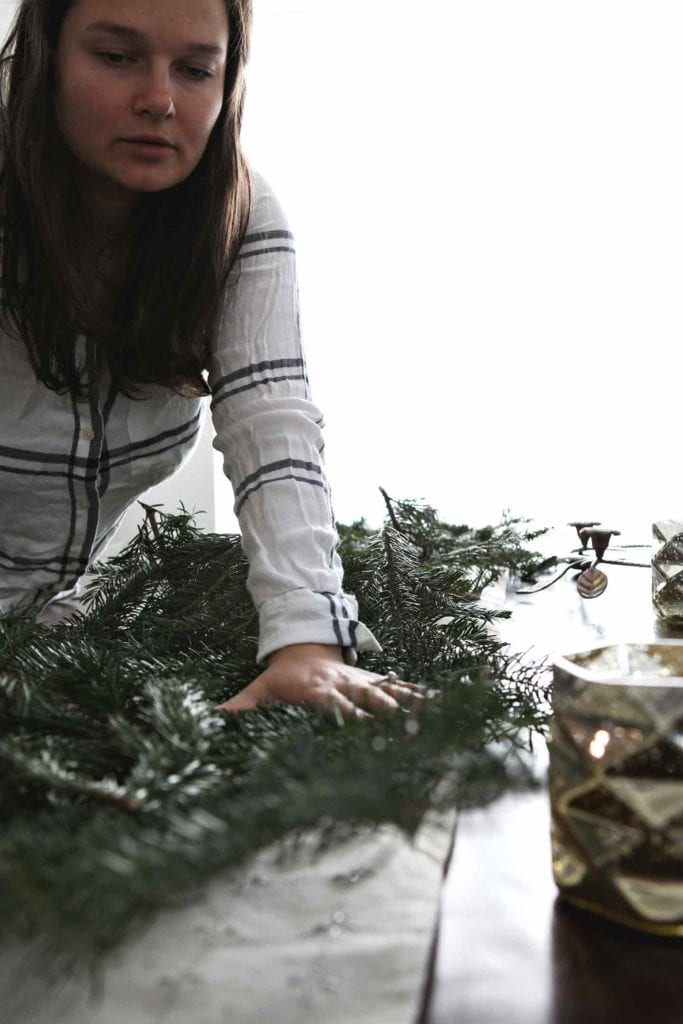 A woman decorates a holiday brunch table with fresh evergreen branches